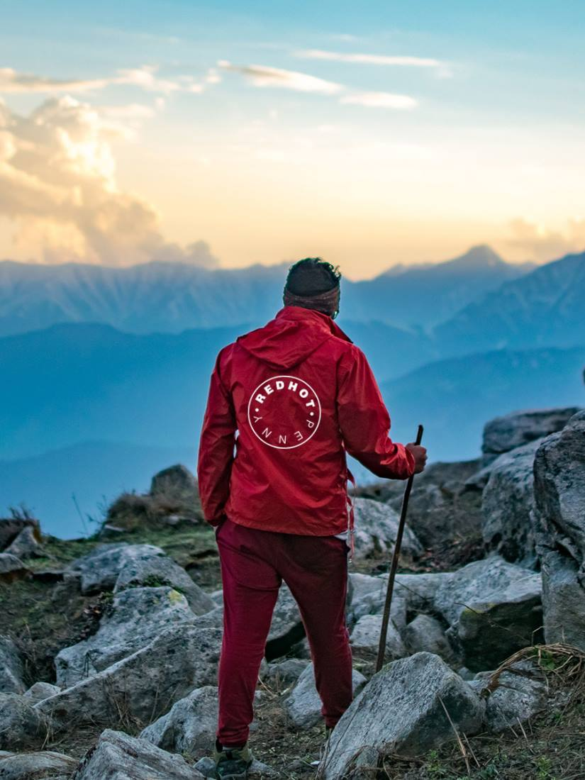 A climber in the mountains, wearing a red windbreaker jacket with the Red Hot Penny logo on the back.
