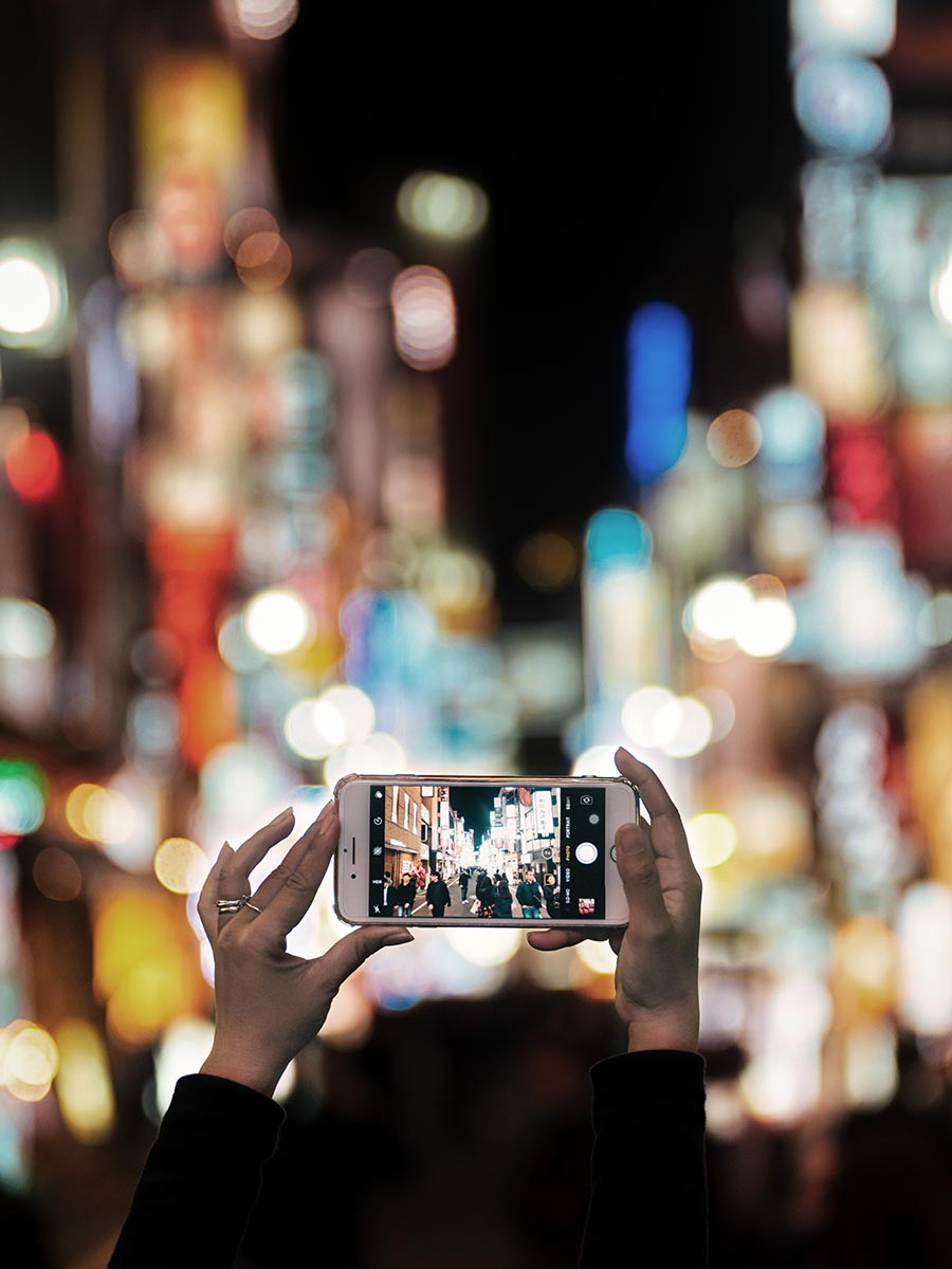 Person taking a photo on their iphone on a lit street