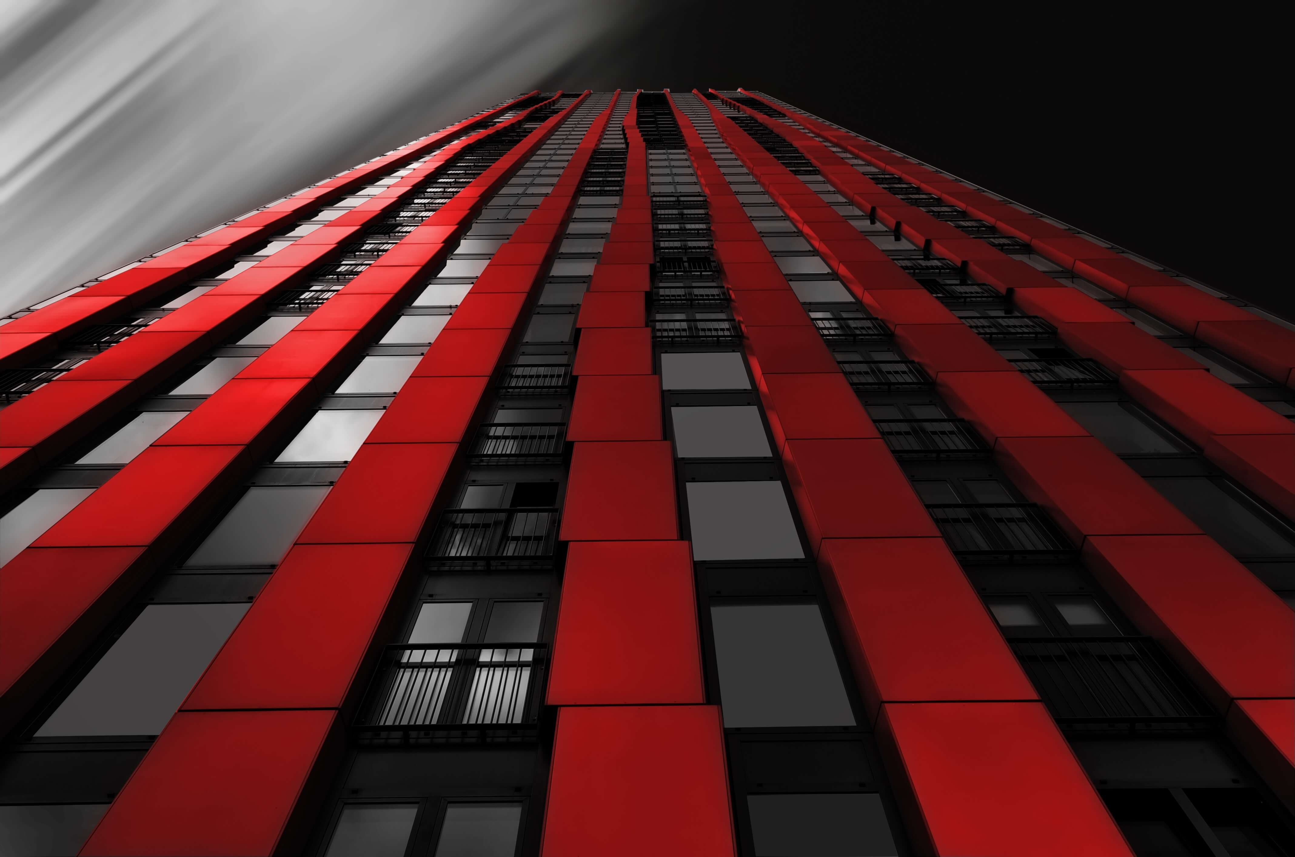 Tall towering building with red panels running in columns