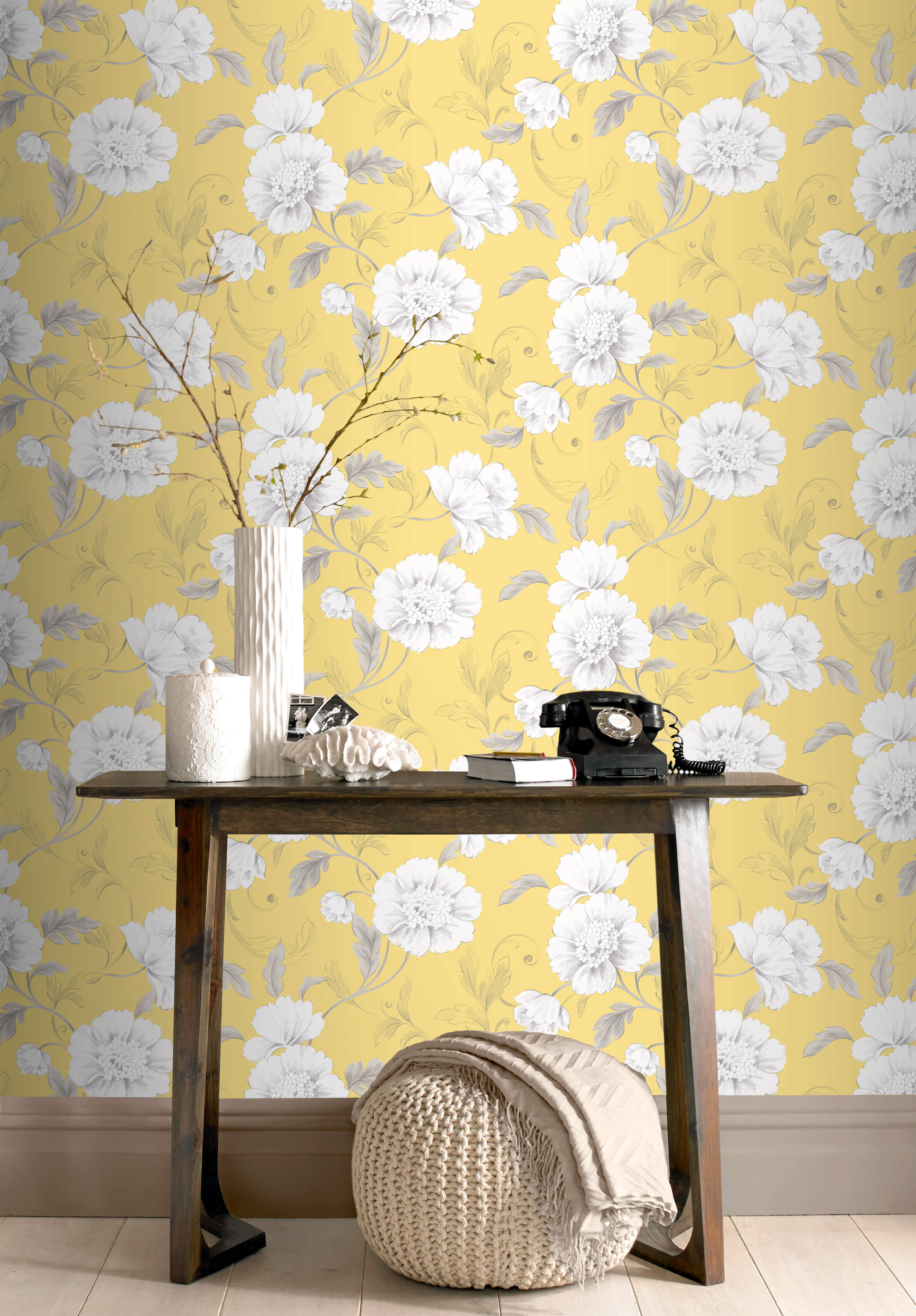 A hallway in a home with yellow floral wallpaper and a dark wood table
